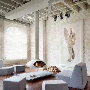 Idee per un soggiorno industriale di medie dimensioni e aperto con pareti bianche, pavimento in legno massello medio, camino sospeso, sala formale, cornice del camino in metallo, nessuna TV e pavimento marrone