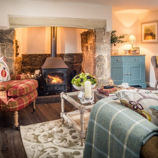 Inspiration for a medium sized farmhouse formal enclosed living room in Devon with white walls, medium hardwood flooring, a wood burning stove, a stone fireplace surround and brown floors.