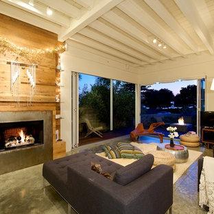 サンディエゴのビーチスタイルのおしゃれなリビング (フォーマル、ベージュの壁、コンクリートの床、標準型暖炉、据え置き型テレビ) の写真