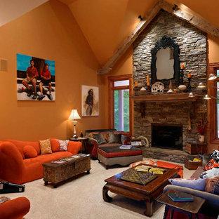 Ejemplo de salón para visitas tradicional, grande, con parades naranjas, moqueta, chimenea tradicional y marco de chimenea de piedra