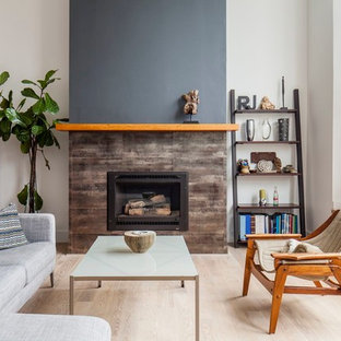 Example of a mid-sized 1950s formal and enclosed light wood floor and beige floor living room design in San Francisco with white walls, a standard fireplace, a stone fireplace and no tv