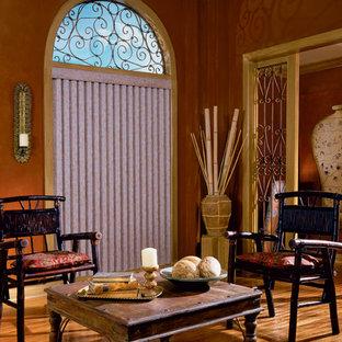 Aménagement d'un très grand salon sud-ouest américain avec un mur orange, un sol en bois clair, aucune cheminée et aucun téléviseur.