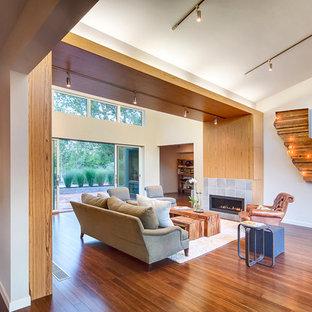 Diseño de salón moderno, extra grande, con paredes blancas, suelo de bambú y marco de chimenea de baldosas y/o azulejos