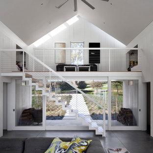Diseño de salón abierto, de estilo de casa de campo, con paredes blancas y suelo de cemento