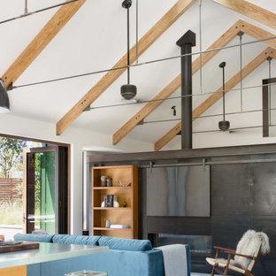 サンフランシスコの中くらいのカントリー風おしゃれなLDK (白い壁、コンクリートの床、両方向型暖炉、金属の暖炉まわり、内蔵型テレビ、グレーの床) の写真