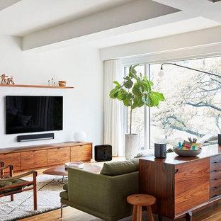 Стильный дизайн: открытая, парадная гостиная комната среднего размера в стиле ретро с белыми стенами, паркетным полом среднего тона, телевизором на стене и коричневым полом без камина - последний тренд