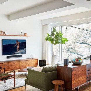 Inspiration för ett funkis vardagsrum, med vita väggar, mellanmörkt trägolv, en väggmonterad TV och brunt golv