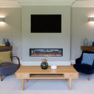 ロンドンのミッドセンチュリースタイルのおしゃれな独立型リビング (グレーの壁、淡色無垢フローリング、横長型暖炉、壁掛け型テレビ) の写真