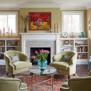 Foto di un soggiorno classico di medie dimensioni e chiuso con sala formale, pareti gialle, parquet scuro, camino classico, cornice del camino in pietra, nessuna TV e pavimento marrone