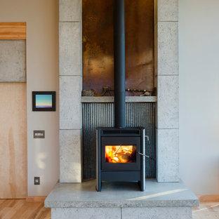 Foto di un piccolo soggiorno design aperto con parquet chiaro, stufa a legna, cornice del camino in cemento e nessuna TV