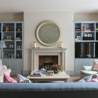 Idee per un soggiorno classico di medie dimensioni con pareti beige, camino classico, cornice del camino in legno, parete attrezzata, libreria, parquet chiaro e pavimento marrone