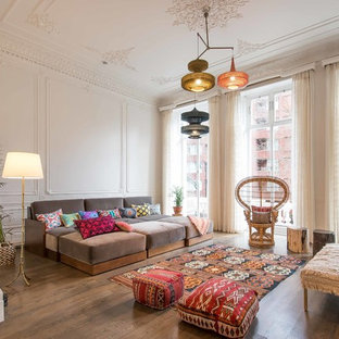 Mid-sized eclectic enclosed medium tone wood floor and brown floor living room photo in London with beige walls