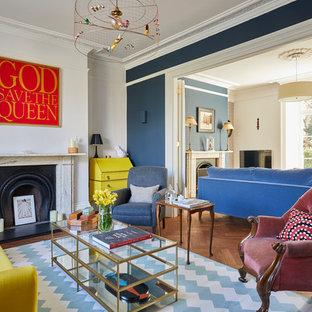 Esempio di un grande soggiorno vittoriano chiuso con pareti blu, pavimento in legno massello medio, cornice del camino in pietra e pavimento marrone