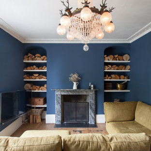 Medium sized classic living room in London with blue walls, medium hardwood flooring, a standard fireplace, a wall mounted tv and brown floors.