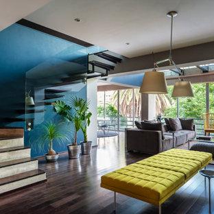 マイアミのトロピカルスタイルのおしゃれなリビング (緑の壁、濃色無垢フローリング、茶色い床) の写真