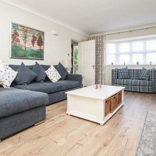 Modelo de salón para visitas abierto, minimalista, grande, con suelo laminado, paredes beige, chimenea tradicional, marco de chimenea de yeso, televisor independiente y suelo beige
