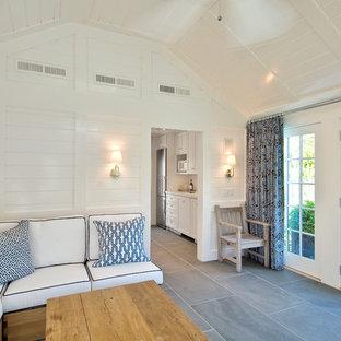 Exemple d'un salon bord de mer avec un sol en ardoise, un mur blanc et un sol gris.