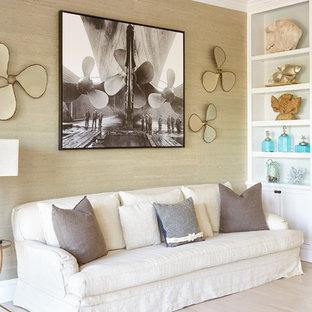 ニューヨークの巨大なビーチスタイルのおしゃれな独立型リビング (ライブラリー、ベージュの壁、淡色無垢フローリング、標準型暖炉、レンガの暖炉まわり、テレビなし、ベージュの床) の写真