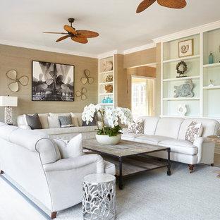 ニューヨークの巨大なビーチスタイルのおしゃれな独立型リビング (ライブラリー、ベージュの壁、淡色無垢フローリング、テレビなし、標準型暖炉、レンガの暖炉まわり、ベージュの床) の写真