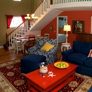 Inspiration for a mid-sized beach style formal and open concept dark wood floor and brown floor living room remodel in Orange County with red walls, a standard fireplace, a brick fireplace and no tv