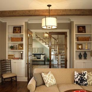 Imagen de salón cerrado, campestre, pequeño, con paredes beige, suelo de madera oscura, chimenea tradicional, marco de chimenea de ladrillo y televisor colgado en la pared