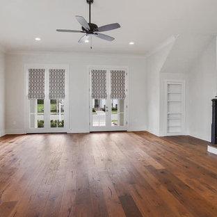Foto de salón abierto, tradicional renovado, con paredes blancas, suelo de madera en tonos medios, marco de chimenea de piedra y televisor en una esquina