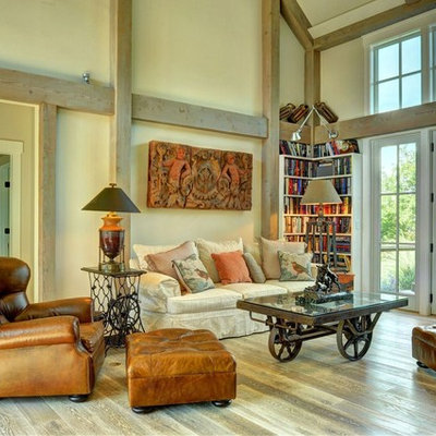 Example of a large country open concept light wood floor living room library design in Burlington with beige walls
