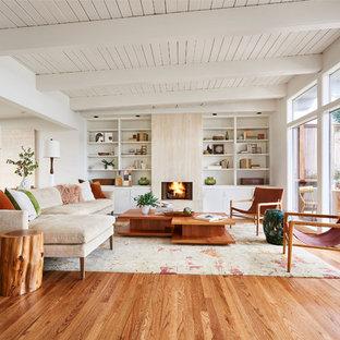 ポートランドの広いコンテンポラリースタイルのおしゃれなLDK (白い壁、無垢フローリング、標準型暖炉、茶色い床、ライブラリー) の写真