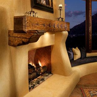 フェニックスのサンタフェスタイルのおしゃれなLDK (テラコッタタイルの床、標準型暖炉、漆喰の暖炉まわり) の写真