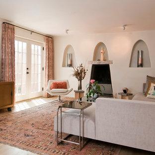 アルバカーキの広いサンタフェスタイルのおしゃれなリビング (白い壁、淡色無垢フローリング、標準型暖炉、漆喰の暖炉まわり、据え置き型テレビ) の写真