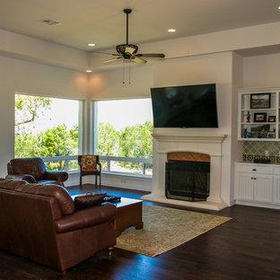 オースティンの大きいサンタフェスタイルのおしゃれなLDK (フォーマル、白い壁、濃色無垢フローリング、標準型暖炉、コンクリートの暖炉まわり、壁掛け型テレビ、ベージュの床) の写真