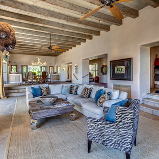 This is an example of an expansive open plan living room in Albuquerque with beige walls, a standard fireplace, a freestanding tv, a plastered fireplace surround and brown floors.