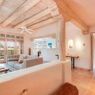 他の地域の中サイズのサンタフェスタイルのおしゃれなLDK (白い壁、テラコッタタイルの床、テレビなし、オレンジの床) の写真