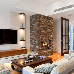 Design ideas for a tropical enclosed living room in Brisbane with white walls, medium hardwood floors, a standard fireplace, a stone fireplace surround and a wall-mounted tv.