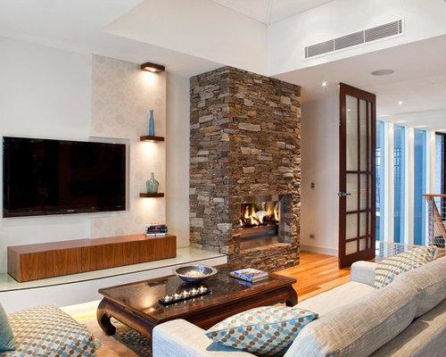 Abgetrenntes Tropenstil Wohnzimmer Mit Weißer Wandfarbe, Braunem Holzboden,  Kamin, Kaminsims Aus Stein Und