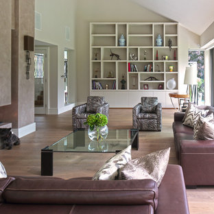 Example of a trendy open concept medium tone wood floor living room design in London with beige walls and a wall-mounted tv