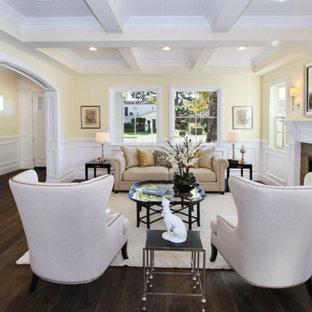 Foto di un soggiorno design di medie dimensioni e aperto con pareti gialle, parquet scuro, camino classico, cornice del camino in mattoni e pavimento marrone