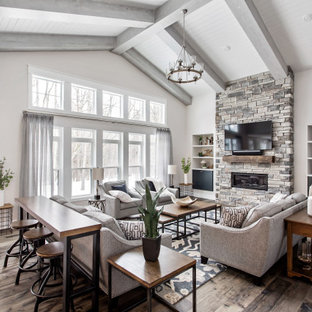 Inspiration for a country open concept dark wood floor, brown floor, exposed beam, shiplap ceiling and vaulted ceiling living room remodel in New York with gray walls, a ribbon fireplace, a stacked stone fireplace and a wall-mounted tv