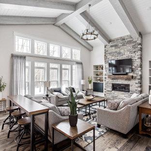 Cette photo montre un salon nature ouvert avec un mur gris, un sol en bois foncé, une cheminée ribbon, un manteau de cheminée en pierre de parement, un téléviseur fixé au mur, un sol marron, un plafond en poutres apparentes, un plafond en lambris de bois et un plafond voûté.