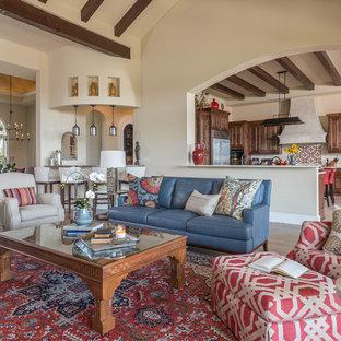Idées déco pour un grand salon sud-ouest américain ouvert avec un mur beige, un sol en bois brun, une cheminée standard, un téléviseur fixé au mur et un manteau de cheminée en carrelage.