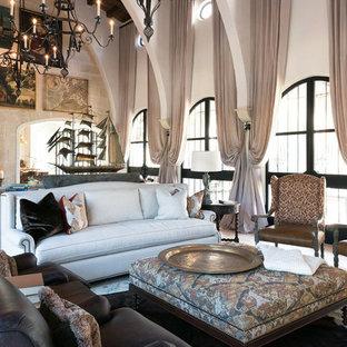 Immagine di un grande soggiorno mediterraneo chiuso con sala formale, pavimento in pietra calcarea, camino classico, cornice del camino in intonaco e nessuna TV