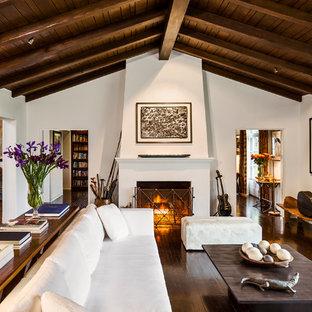 サンタバーバラの広い地中海スタイルのおしゃれな独立型リビング (白い壁、濃色無垢フローリング、標準型暖炉、漆喰の暖炉まわり) の写真