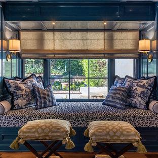 サンタバーバラの広い地中海スタイルのおしゃれなLDK (ライブラリー、青い壁、濃色無垢フローリング、標準型暖炉、石材の暖炉まわり、テレビなし、茶色い床) の写真