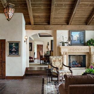 サンディエゴの広い地中海スタイルのおしゃれなLDK (ベージュの壁、テラコッタタイルの床、石材の暖炉まわり、テレビなし、フォーマル、標準型暖炉、茶色い床) の写真