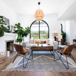 Foto på ett mellanstort medelhavsstil allrum med öppen planlösning, med ett finrum, vita väggar, mellanmörkt trägolv, en standard öppen spis, en spiselkrans i gips och brunt golv