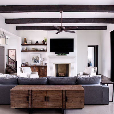 Example of a mid-sized transitional formal and open concept gray floor and concrete floor living room design in Austin with white walls, a standard fireplace, a wall-mounted tv and a plaster fireplace