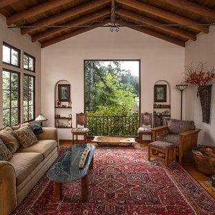 Imagen de salón para visitas mediterráneo, sin televisor, con paredes blancas, suelo de madera en tonos medios, chimenea tradicional y marco de chimenea de yeso