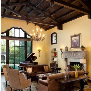 Ispirazione per un ampio soggiorno mediterraneo aperto con sala formale, pareti gialle, camino classico, cornice del camino in pietra e nessuna TV