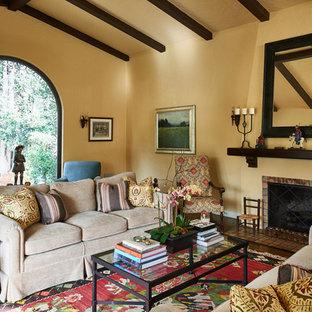 ロサンゼルスの広い地中海スタイルのおしゃれな独立型リビング (フォーマル、ベージュの壁、濃色無垢フローリング、標準型暖炉、タイルの暖炉まわり、テレビなし、茶色い床) の写真