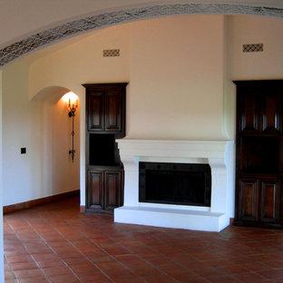 サンタバーバラの中くらいの地中海スタイルのおしゃれな独立型リビング (白い壁、標準型暖炉、壁掛け型テレビ、テラコッタタイルの床、赤い床) の写真